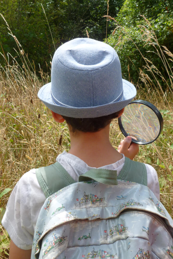 Boy with magnifying glass (copyright Avon Gorge and Downs Wildlife Project)
